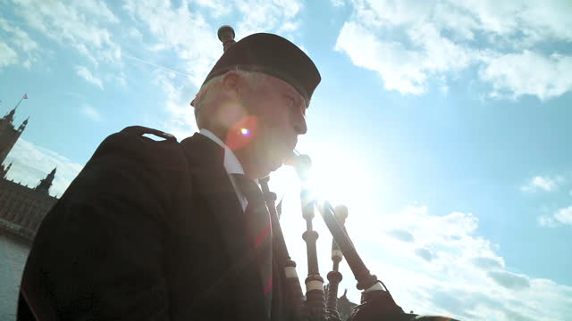 traditional bagpipe player performs on westminster bridge with lens flare. - house of commons stock videos & royalty-free footage