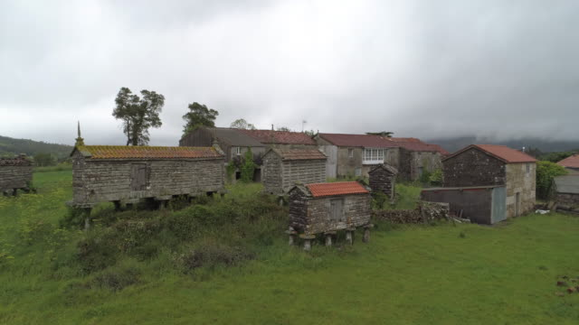 traditional barns by houses in village against cloudy sky - galicia, spain - galicia stock videos & royalty-free footage