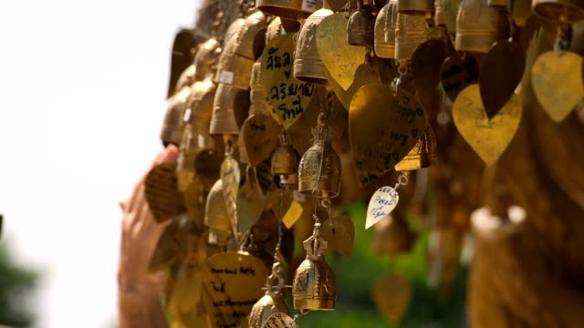 traditional bells with wishes near buddhist temple close-up - temple body part stock videos and b-roll footage
