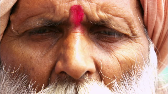 """a traditional """"bindi"""" adorns the forehead of a hindu man. available in hd. - bindi stock videos and b-roll footage"""
