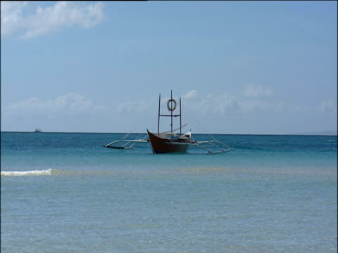vidéos et rushes de traditional boat with stabilising floats on calm blue sea philippines - bercement