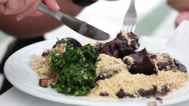 vídeos de stock, filmes e b-roll de prato tradicional brasileiro - feijoada - tradição