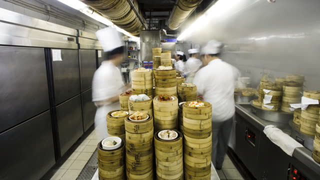 Traditional Chinese Rice and Dim Sum Steamers being prepared in a busy restaurant kitchen, Central, Hong Kong, China - model and property released -Time-lapse