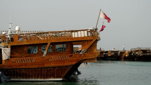 traditional dhow boats in in the doha port corniche in doha bay, doha, qatar. 4k resolution. - ダウ船点の映像素材/bロール