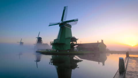 stockvideo's en b-roll-footage met traditional dutch windmills in the mist during sunrise along a canal at the zaanse schans in the netherlands - verwerkingsfabriek