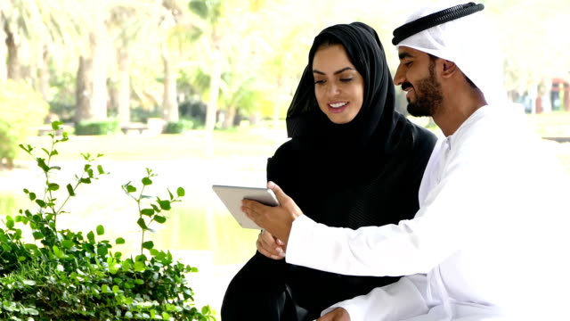 Traditional Emirati young couple outside with digital tablet - slowmotion