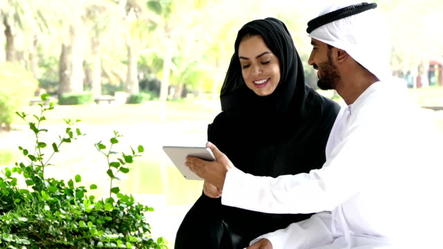 vídeos de stock e filmes b-roll de traditional emirati young couple outside with digital tablet - arábia saudita