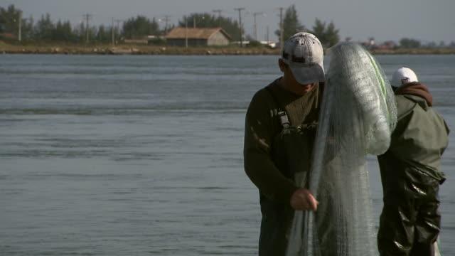 Traditional fisherman fixes net, unaware of dolphin breaching behind him, Laguna, Brazil [Brasil]