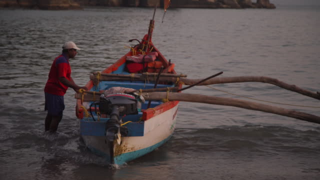 traditional fishermen bringing boats to shore - india - goa stock videos & royalty-free footage