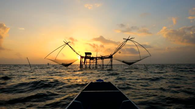stockvideo's en b-roll-footage met traditionele vissers net vissen in het meer bij zonsopgang. thaise stijl visserij val in het zuiden van thailand, 4k. - visser