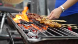 Traditional grilled meat on sticks cooked at street local market. Satay bbq. Closeup. 4k