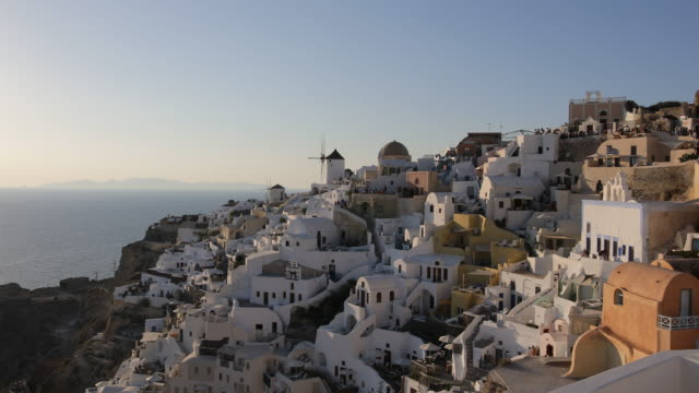 traditional houses during the sun set at oia caldera with views to the sea caldera and volcano. - oia santorini stock videos & royalty-free footage