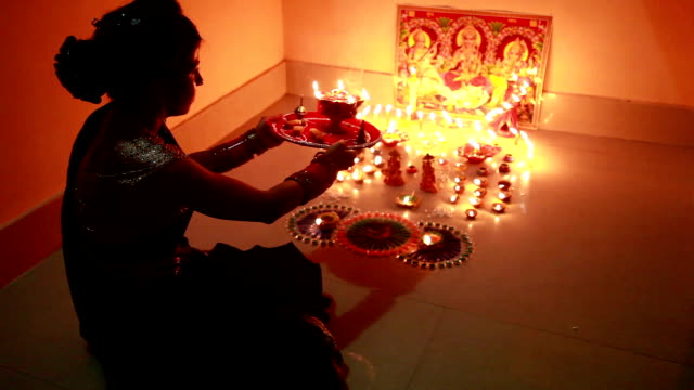 Traditional Indian woman worshiping Lakshmi on Diwali festival