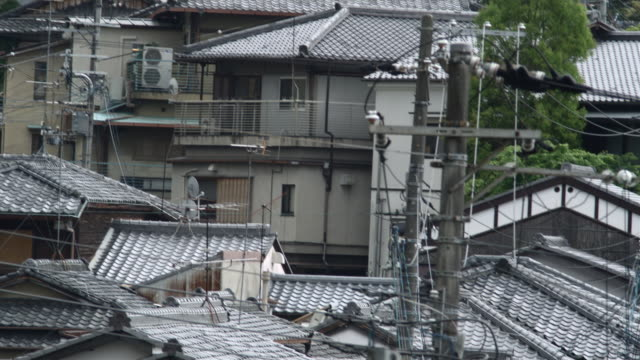 ms td traditional japanese roofs and tourists on narrow street, kyoto, japan - ケーブル線点の映像素材/bロール