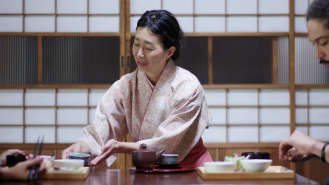 Traditional Japanese Ryokan owner pouring tea for tourists