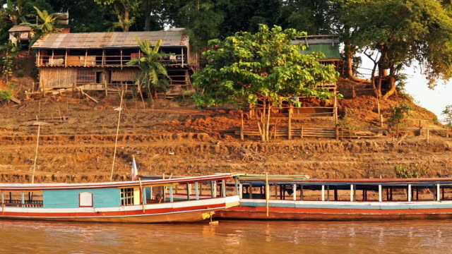 traditional mekong river cruise tourboat and stilt house, luang prabang, laos - stilt house stock videos & royalty-free footage