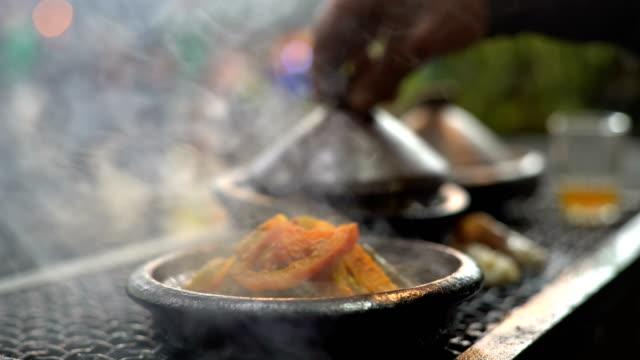 vidéos et rushes de traditional moroccan cuisine, tajine tagine dish vapour vapour at night - maroc
