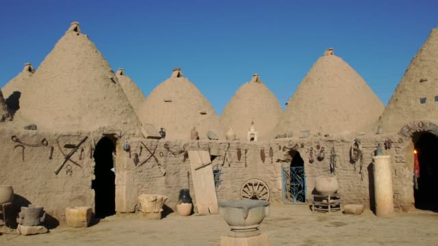 vídeos de stock, filmes e b-roll de traditional mud brick buildings in harran, turkey, topped with domed roofs and constructed from mud and salvaged brick. - arcaico