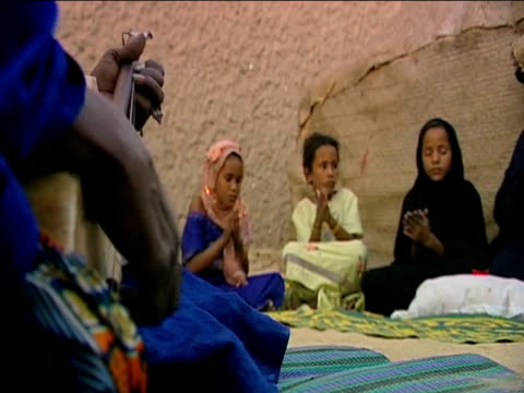 Traditional musician plays music by campfire as group of women and children clap Timbuktu; 30 November 2009