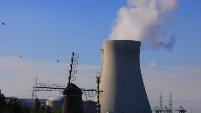 a traditional old flemish mill stands next to the cooling towers of doel nuclear plant belching steam on july 13 2020 in beveren belgium doel power... - uranium stock videos & royalty-free footage