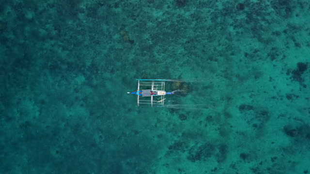 Traditional Philippines fishing boat with outriggers sailing on the clear lagoon.