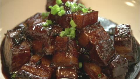 vídeos y material grabado en eventos de stock de traditional red braised pork served onto a plate - grasa nutriente