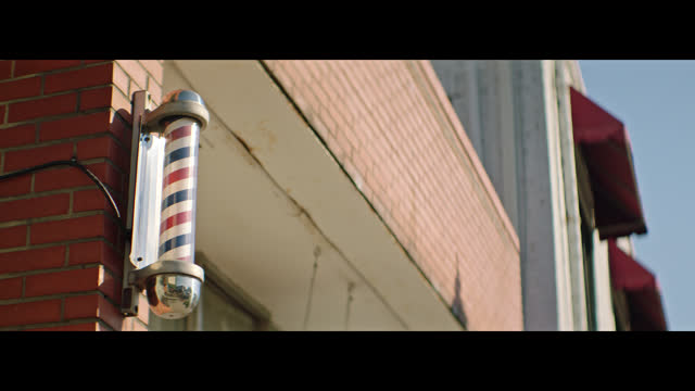 traditional red, white, and blue striped barber shop pole turns on outside of small town brick and mortar barber shop. - barber stock videos & royalty-free footage