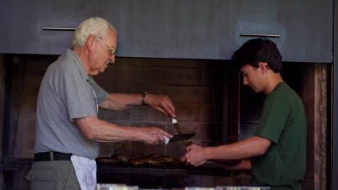 vídeos y material grabado en eventos de stock de tradicional reencuentro de la familia argentina - asado alimento cocinado