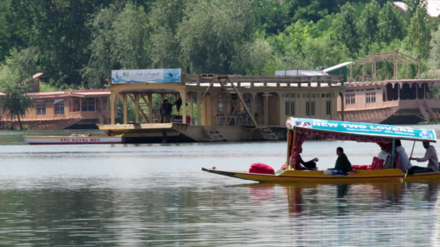 vídeos de stock e filmes b-roll de a traditional shikara, flat bottomed rowboat, rowing in the dal lake with houseboats in the background in kashmir - barco casa