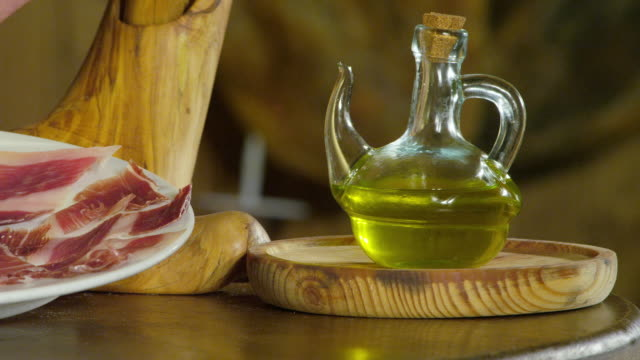 cu pan traditional spanish food: olives, pata negra ham and olive oil - decanter stock videos and b-roll footage