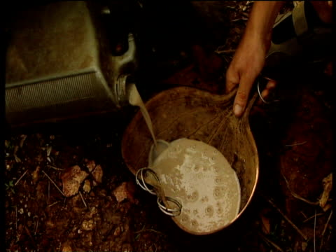 traditional suri geso beer is poured from plastic container into dried gourd suri territory ethiopia - zucca legenaria video stock e b–roll