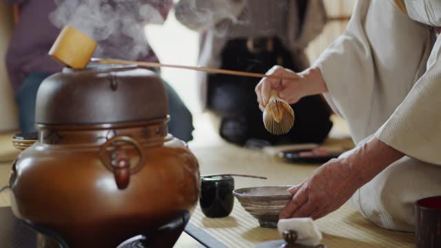 vídeos de stock, filmes e b-roll de anfitrião tradicional da cerimónia de chá que eleva e que usa whisk - washitsu