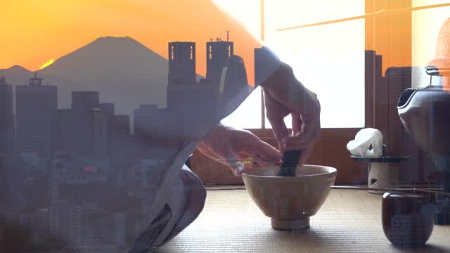 """vidéos et rushes de cérémonie traditionnelle de thé """"sado"""" avec le mont fuji avec le bâtiment de la ville avant le coucher du soleil - céramique"""