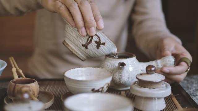 vídeos y material grabado en eventos de stock de elaboración de té tradicional - pouring black tea into cup - ceremonia