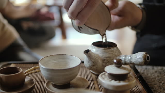 traditional tea making - pouring black tea into cup - tea cup stock videos & royalty-free footage