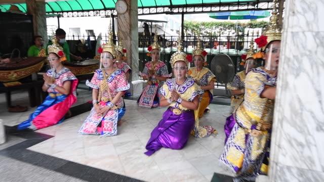 traditional thai dancers wearing face shields perform at the erawan shrine on august 6, 2020 in bangkok, thailand. - エラワン聖堂点の映像素材/bロール