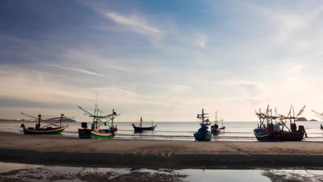 vídeos de stock e filmes b-roll de tailandês tradicionais barcos de pesca ancorados na praia ao nascer do sol - peixe fresco