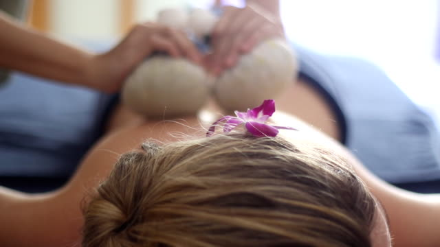 traditional thai herbal compress massage - massaging stock videos and b-roll footage
