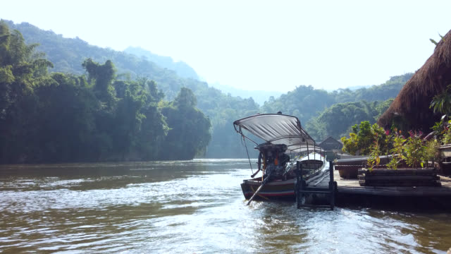 traditional thai long tail boat on river kwai in kanchanaburi, thailand - bamboo shoot stock videos & royalty-free footage