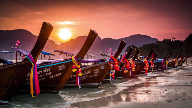 traditional thai longtail boats under beautiful sunset sky in the  krabi province. phi phi islands, thailand. - romantic sky stock videos & royalty-free footage