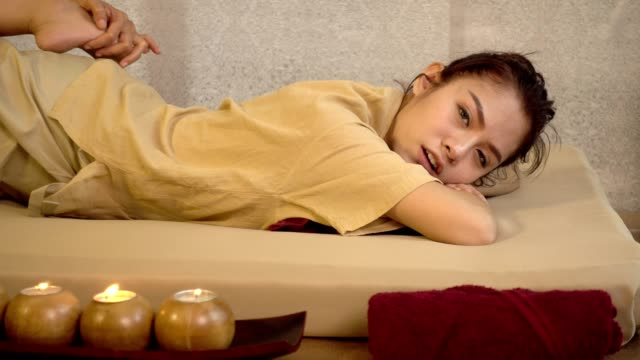 vídeos de stock e filmes b-roll de traditional thai massage, young beautiful woman relaxing in spa salon and receiving head or face massage - cultura tailandesa