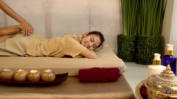 Traditional Thai Massage, Young beautiful woman relaxing in spa salon and receiving head or face massage