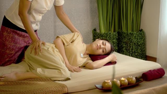 vídeos y material grabado en eventos de stock de masaje tradicional tailandés, hermosa joven relajante en el salón de spa y recibir masaje de cabeza o la cara - tratamiento de spa
