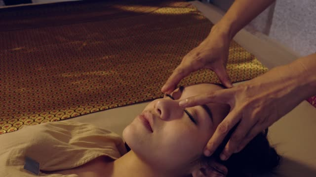 vídeos de stock e filmes b-roll de traditional thai massage, young beautiful woman relaxing in spa salon and receiving head or face massage - tratamento em spa