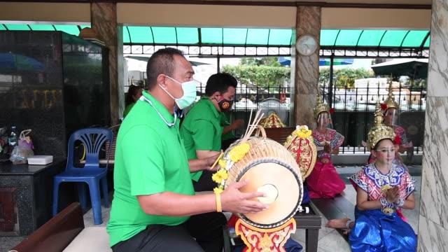 traditional thai musicians wearing face shields perform at the erawan shrine on august 6, 2020 in bangkok, thailand. - エラワン聖堂点の映像素材/bロール