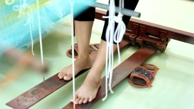 Traditional Thai silk weaving by using the loom.