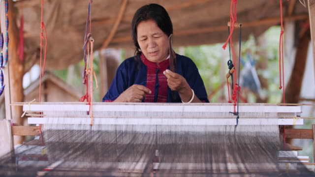 traditional thai textile manufacture in craft village, old women work on wooden weaving thread machines and spin yarn creating cotton fabric. - civiltà maya video stock e b–roll