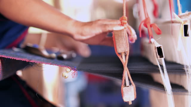 traditional thai textile manufacture in craft village, old women work on wooden weaving thread machines and spin yarn creating cotton fabric. - embroidery stock videos & royalty-free footage