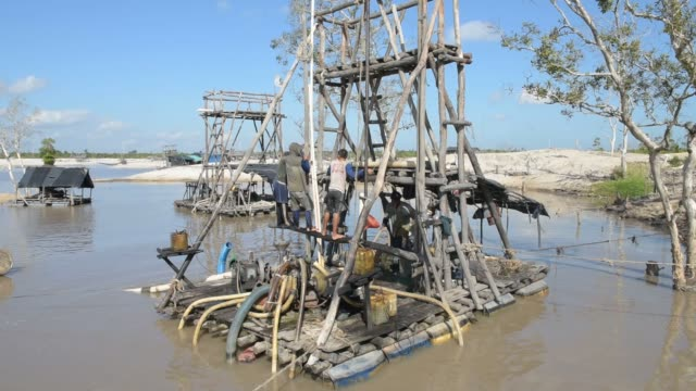 traditional tin mining is shown in bangka island, indonesia on wednesday, july 29, 2015 shots: full wide shot of mining dredger as workers work, man... - tin mine stock videos & royalty-free footage