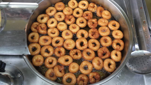 stockvideo's en b-roll-footage met traditionele turkse desseert lokma, stroop donut, maken en bakken van lokma dessert in een grote pan in olie, begrafenis weggeven, lokma voedsel, turkse baklava - turks fruit